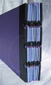 Spine detail of the book, showing the beads and wire binding